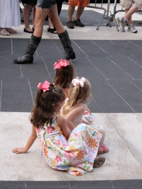 Three little girls sitting on Josie Robertson Plaza, mesmerized by Asphalt Orchestra.